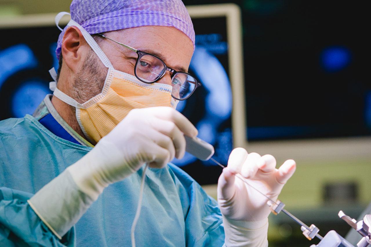 Bei der tiefen Hirnstimulation implantiert der Neurochirurg Prof. Dr. med. Claudio Pollo der Patientin in einem minimalinvasiven neurochirurgischen Präzisionseingriff kleinste Elektroden im Gehirn.